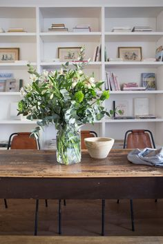 Comedor con mesa de madera recuperada, gran librería y ramo de liliums y eucalipto 00449769 O