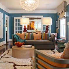 Eclectic Living white trim Design Ideas, Pictures, Remodel and Decor  blue walls | flower chandelier | round coffee table | retro chair | gray couch | dark wood floors | interior design
