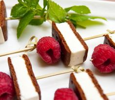 Mini ice cream sandwiches with a raspberry and mint garnish.