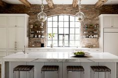 White kitchen with marble worktops, exposed bricks and beams and wonderful pendant lights