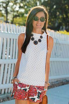 white high neck sleeveless eyelet shirt, white shorts with large red/fuschia flowers. Preppy fashion