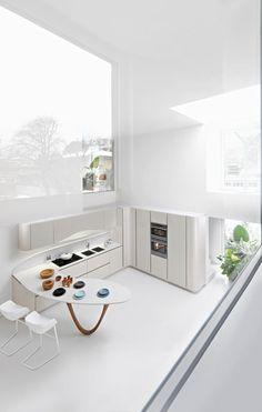 白いインテリア。白いキッチンです。モダンなデザインのきっちんは、外にほとんど物が出ていません。食品のパッケージや調理器具などをしまうことで、色の氾濫をおさえているのですね。カーブしたテーブルがかわいらしいですね。