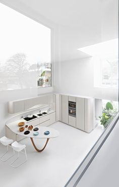 Check out the curve of the island and its legs. As well as the curve of the above counter storage  Modern White Kitchen By Snaidero