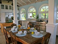 This blue and white country cottage kitchen features white cabinets, white columns, and arched picture windows.  A rustic farmhouse table with intricate wood carvings serves as the focal point of the room.  A vaulted ceiling extends the space and gives this kitchen an open, airy feel.