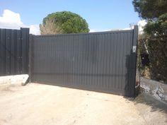 Puerta corredera construida en tubo de 50 mm, construida en chapa de lama de puertas, pintada en color negro forja y motorizada por medio de un motor de la marca CAME.