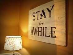 "My distressed ""Stay for Awhile"" sign welcomes guests into the cozy kitchen."