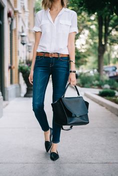 White blouse, belted jeans, pointed flats.
