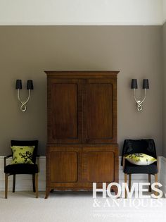 Regency mahogany clothes press.  A neutral backdrop and simple symmetrical styling set off the richness of dark woods.
