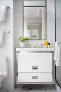 2 towel bars above toilet + modern vanity. Philip House white bathroom designed by Victoria Hagan. Love the cabinetry.