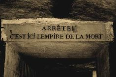 """To get to the catacombs, visitors are advised to take the metro and get off at the Denfert Rocherea station. At the entrance to the catacombs, there is a gate with a sign saying """"Arrête! C'est ici l'empire de la Mort"""" which means """"Stop! Here lies the Empire of Death""""."""