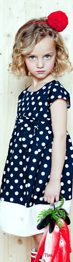 White polka dots on blue dress, the white and blue always works well together! Oh, and there's a red dot on her headband. Super cute!
