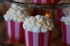 """For my Oscar party next year!  Popcorn cupcakes:   1. pull apart mini marshmallows and stick them back together, pinching and twisting to make """"kernels""""  2. roll a baked, frosted cupcake in the """"kernels"""" and brush a little watered-down yellow food coloring on them to create """"butter"""".   3. add striped liners and a little edible gold glitter and serve!"""