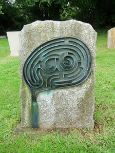 """A Gravestone. On the reverse it reads: Michael Ayrton  Painter and Sculptor, 1921 - 1975  Elisabeth Ayrton, Writer, 1910 - 1991  Michael Ayrton wrote and created many works associated with the myths of the Minotaur and Daedalus, the legendary inventor and maze builder, including a bronze sculpture and the pseudo-autobiographical novel """"The Maze Maker"""""""