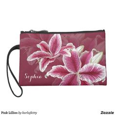 """Pink Lillies Wristlet  A ruby background color with painted stargazer lillies in shades of pink, red, and white.  Add your name to the text field or clear it out if wish.  You can also click on """"Customize It!"""" to adjust the font type, size, color, placement, etc.  Artwork and design by Karlajkitty."""