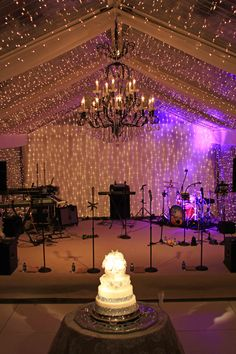 Our large black metal and crystal chandelier creates a focal point on the dance floor and a lovely setting for wedding cake photos. A clear tent encased in twinkle lights and spot lights for the cake complete the lighting installation by Get Lit, Special Event Lighting.  Event design by Walton Event Design.