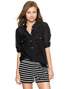 Tunic blouse with black and white striped shorts.