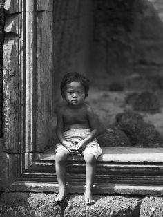 Angkor Wat Pensive  Photo and caption by Dean Yeadon    The son of a worker in the Angkor Wat ruins watches the world go by.  Location: Angkor Wat, Cambodia