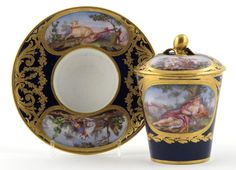 A Sèvres cabinet cup with cover and trembleuse saucer c.1784, the cup painted with a reclining maiden beside a basket of flowers on a grassy hillock, the cover and saucer with panels of animals and doves with baskets, hats and musical instruments, reserved on a bleu-de-roi ground with raised gilt garlands and scrolls, interlaced LL marks and date code for 1784, painter's mark for Chabry, 15cm. (3)