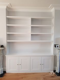 Traditional fitted cupboards with modern floating book shelves above. Fitted into an alcove space to create more storage for books and other items