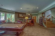 Traditional Basement with flush light, High ceiling, Built-in bookshelf, Carpet, stone fireplace, Exposed beam, Ceiling fan