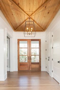 Wood doors, ship lap farmhouse.  Wood plank ceiling.  LOVE the chandelier in this entryway or foyer.