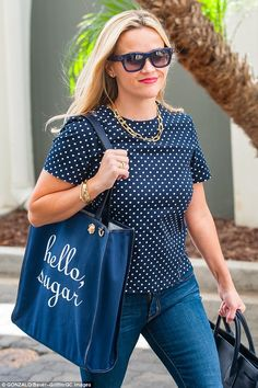 Representing! Aside from her navy leather handbag, Witherspoon also hauled a Draper James ...