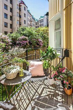 balcon-fleuri-table-et-chaise-gris-coussin-rose-pastel-tapis-a-franges