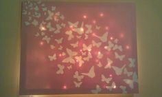 Butterfly stickers from dollar store, spare can of spray paint and a canvas. Place stickers, spray, then remove stickers. Hang Christmas behind the canvas for a wall night light!