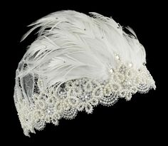 This ivory bridal cap is made of delicate floral lace. The edge is trimmed with an elegant ivory pearl design with a few rhinestones. The centerpiece is a fan of beautiful feathers embellished with a few rhinestones, teardrop jewels and flowers.