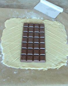 3. Lägg chokladkakan ovanpå degen. Skär kanterna i sneda flikar.