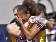 Jamaica's Brigitte Foster-Hylton is consoled by Australia's Sally Pearson after competing in a women's 100-meter hurdles heat during the athletics in the Olympic Stadium at the 2012 Summer Olympics, London, Monday, Aug. 6, 2012.(