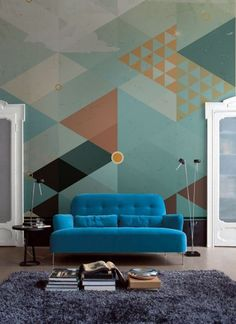 The dominant shape in this picture is triangle. Mainly because of the wall that is painted with different colors of triangles. The lamps on the side of the love seat have a triangular shape to them.