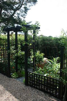 I like this black trellis gate and low fence.  The garden does not appear to be Japanese but the fence lends an Asian influence.