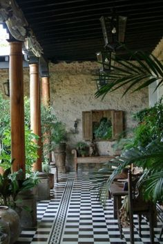 Black and white checkered tile floor with lush potted plants, stucco walls and vintage columns.