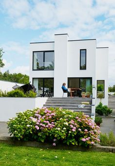 Beautiful white facade on this tall bungalow house with black windows that contrast the white.