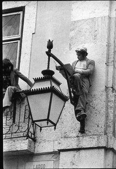 This guy reads. cafeparaacordarosmortos: Homem lê o jornal, sentado num candeeiro público, enquanto uma revolução acontece debaixo dele. Lisboa, 25 de Abril de 1974 Carlos Gil