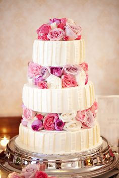 Vanilla buttercream cake filled with pink, mauve and ivory roses between tiers