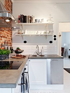 Beautiful light in this white space with exposed brick statement wall and stainless steel appliances. Love the open shelving.