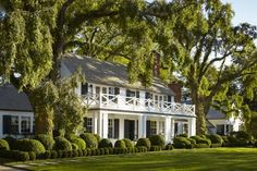 White house, black shutters, lush green landscaping