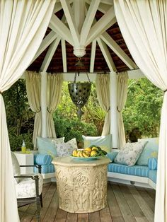 Exposed wood and heavy curtains make this outdoor gazebo cool and inviting. The plush banquet provides ample shading while the pierced-metal lantern gives it a global feel. (Photo: Tria Giovan)