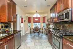 Contemporary Kitchen with Simple granite counters, U-shaped, Flush, Flat panel cabinets, limestone tile floors, High ceiling