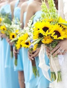 Sunflower yellow bouquets with light blue bridesmaid's dresses.