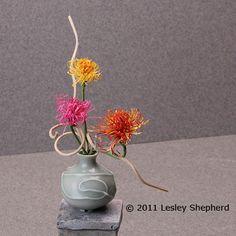 Arrangement of dollhouse scale spider chrysanthemums in a miniature celadon vase.