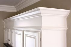 Moldings and trim added to the tops of cabinets make them appear taller and more like high-end custom cabinetry.