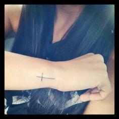 Little wrist tattoo of a cross.
