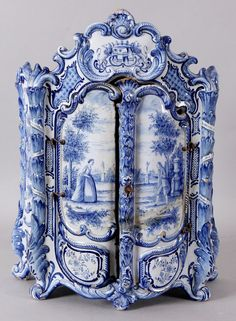 Antiek 19e eeuws Makkums aardewerken (miniatuur) rococokast 2e helft 19e eeuw. Naar 18e eeuws voorbeeld. Blauw decor met figuren in landschap. Gesigneerd T.T. (Tinus Tichelaar) Holland.