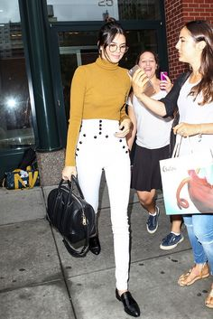 Kendall Jenner pairs Isabel Marant Nepos High-Rise Stretch-Cotton Twill Skinny Pants with an A.L.C ribbed turtleneck and a Givenchy bag.