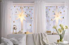 Valkoinen sohva ikkunan edessä. Ikkunassa on isot valkoiset tähdet sekä kullan- ja hopeanvärisiä kuusenkoristeita.