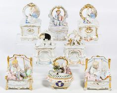 Lot 457: German Child Porcelain Fairing Box Assortment; c.1900, seven boxes with children on dresser, on mantle or in bed; together with a porcelain child fairing ink well; some may be produced by Conta & Boehme