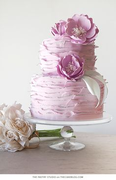 Tiered wedding cake with ruffle design in lilac lavender colour with peony floral decoration for spring summer weddings